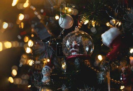 Photo pour Décorations de Noël sur pin avec bokeh lumière floue, jouet mignon du Père Noël et ampoules suspendues sur l'arbre de Noël. - image libre de droit