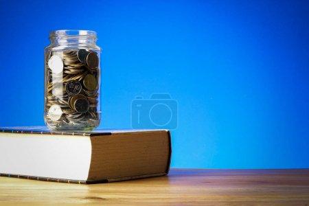 Photo pour FONDS D'ÉDUCATION CONCEPT avec des pièces dans un bocal en verre et un vieux livre . - image libre de droit