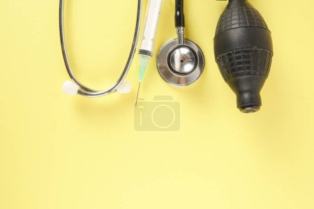 Medical Concept with stethoscope ,syringe  isolated on yellow background. Copy Space