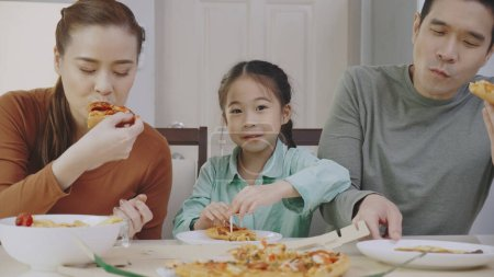 Photo for Family Asian people are happy to eat enjoy tasty pizza at home. Parents and daughter eating delicious Italian food from takeaway delivery. Concept food takeout - Royalty Free Image
