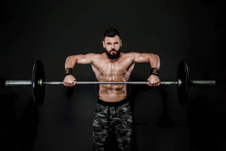 Photo for Athletic muscular man workout with barbell . Strong bodybuilder with naked torso - Royalty Free Image