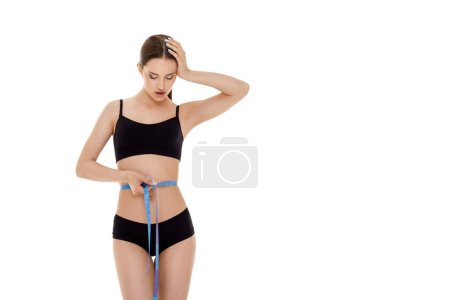 Photo for Beautiful woman measuring perfect waist with blue measuring tape. slim body isolated on white background - Royalty Free Image