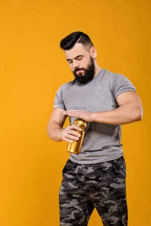 Photo for Handsome strong man drinks water on yellow background - Royalty Free Image