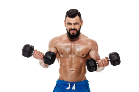 Photo for Athletic muscular man doing exercises with dumbbells. Strong bodybuilder with naked torso on white background - Royalty Free Image