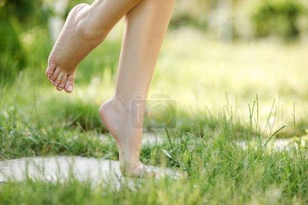 Foto de Hermosa mujer pies descalzos caminando sobre la hierba verde en verano - Imagen libre de derechos