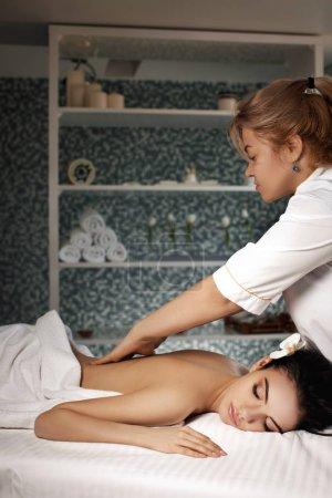 Photo for Relaxed beautiful young woman receiving massage in spa salon. Beauty treatment - Royalty Free Image