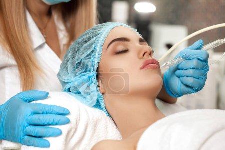 Photo pour Esthéticienne fait le nettoyage ultrasonique du visage dans le salon de spa. cosmétologie - image libre de droit