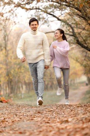 Photo pour Couple amoureux marchant dans un magnifique parc d'automne. souriant homme et femme se tenant la main et s'amusant. moments heureux de la vie . - image libre de droit