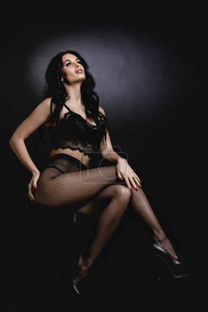 Photo pour Femme sexy en lingerie sensuelle dentelle noire, collants et talons hauts avec long cheveux bouclés assis sur la chaise en studio. - image libre de droit