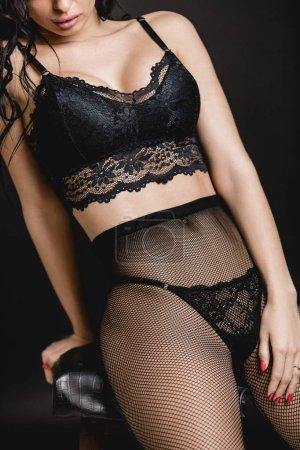 Photo pour Femme sexy en lingerie sensuelle dentelle noir et collant sur fond noir. corps de la femme de jeune femme séductrice dans érotiques bas, culotte et soutien-gorge - image libre de droit