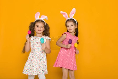 Photo for Two little girls with Easter bunny ears holding colorful eggs on yellow background. Happy easter. cute children - Royalty Free Image