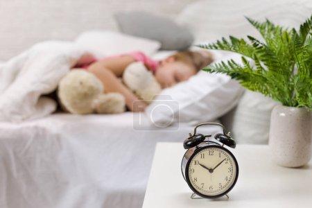 Photo pour Petite fille mignonne dormant avec un ours en peluche dans son lit - image libre de droit