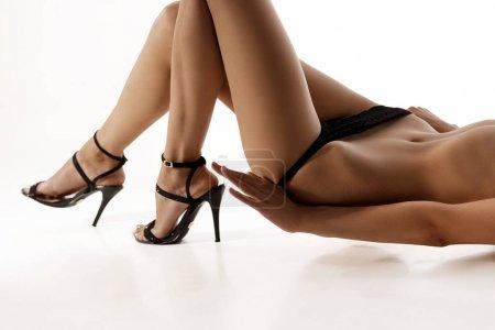 Photo pour Parfait belle jeune femme sexy en noir chaussures à talons hauts en pose érotique sur fond blanc. corps nu de sensualité dame élégante . - image libre de droit