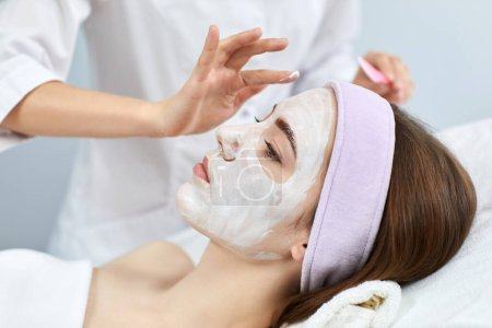 beautician applies the mask to the face of woman