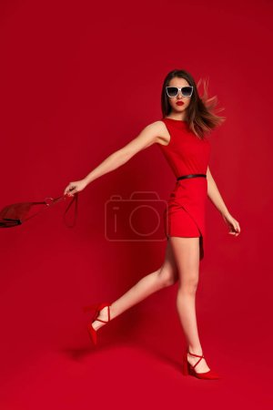 Photo for Gorgeous fashionable woman holding red bag. brunette girl in luxurious sunglasses and red dress on red background. fashion concept - Royalty Free Image