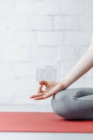 Foto de Mujer practicando yoga en casa. Jnana mudra cierre, hembra, conectando el pulgar y el dedo delantero, formando un círculo, palmas mirando hacia arriba, armonía y concentración de yoga concepto, enfoque a la derecha. - Imagen libre de derechos
