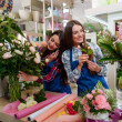 Two girls working in flower shop. Bunches and bouq...
