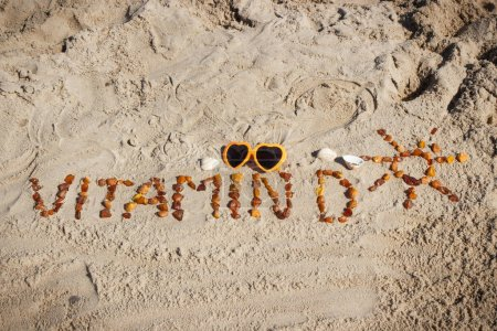 Photo pour Inscription vitamin D with shape of sun made of amber stones and sunglasses on sand at beach. Prevention of vitamin D deficiency - image libre de droit