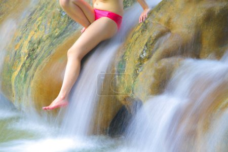 waterfall and leg of woman enjoy in the water.
