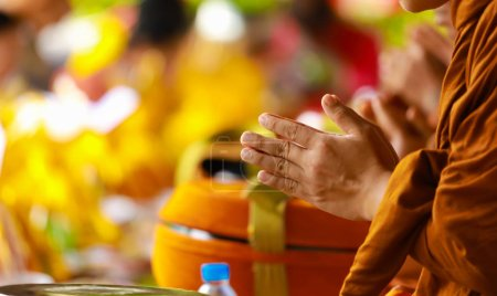 Hand of monk in Buddhist prayer process.