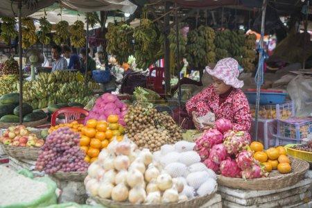 Photo for CAMBODIA, KAMPONG THOM - NOVEMBER, 2017: Seller and fruits at the market Psar Kampong thom in the city of Kampong Thom of Cambodia - Royalty Free Image