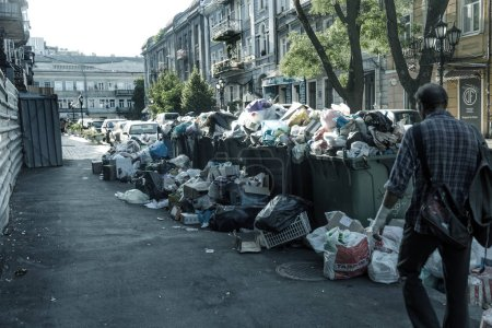 Odessa, UKRAINE - August 25, 2018: Pile of garbage with garbage bags full of garbage cans on city street. Many household waste plastic bags in front of house. Dump, wastes of environmental pollution
