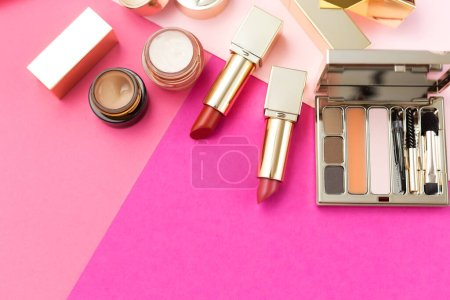 set of cosmetics and accessories on pink background