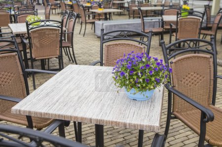 Photo for Terrace cafe table and chairs with beautiful bouquet of flowers on table - Royalty Free Image