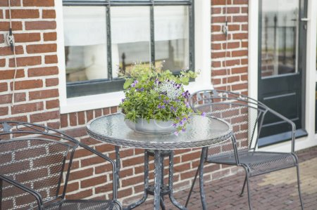 Photo pour Terrasse table basse et chaises avec beau bouquet de fleurs sur la table - image libre de droit