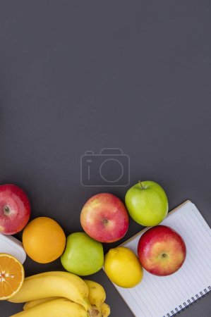 Photo for Fresh fruits and notebook on dark background - Royalty Free Image