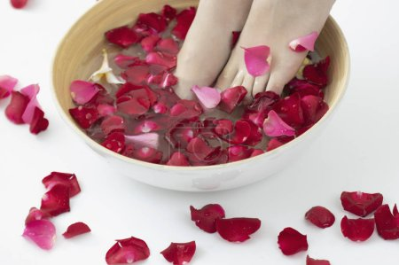 Photo for Woman in spa salon, feet in bowl with rose petals - Royalty Free Image