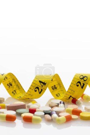 Photo pour Pilules et ruban à mesurer sur le fond blanc. - image libre de droit
