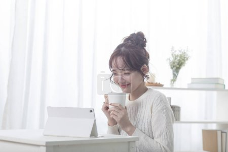 Photo for Happy young Asian woman drinking tea and using tablet pc - Royalty Free Image