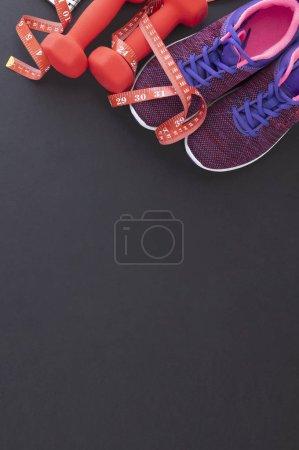 Photo pour Top view of sneakers and dumbbells with measuring tape, sport concept - image libre de droit