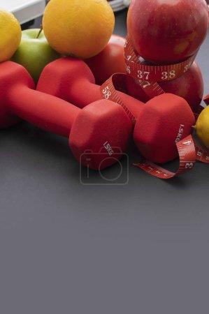 Photo pour Fruits frais, poids et ruban à mesurer sur fond sombre. - image libre de droit