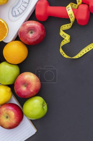 Photo for Fresh fruits, weights, scales and measuring tape on dark background. - Royalty Free Image