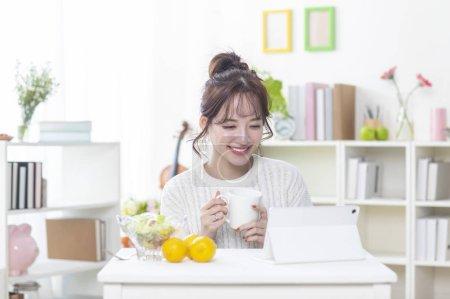 Photo pour Heureux jeune asiatique femme boire du thé et en utilisant tablette pc - image libre de droit