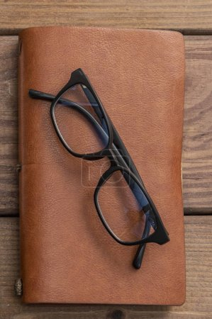 Photo for Old glasses with vintage style notebook on wooden background - Royalty Free Image