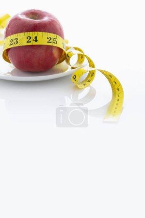 Photo pour Pomme rouge et ruban à mesurer dans une assiette blanche. - image libre de droit