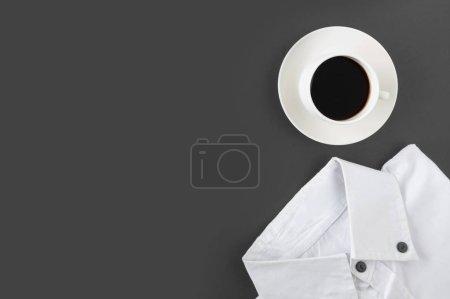 Photo pour Tasse blanche de café et chemise sur fond noir. - image libre de droit
