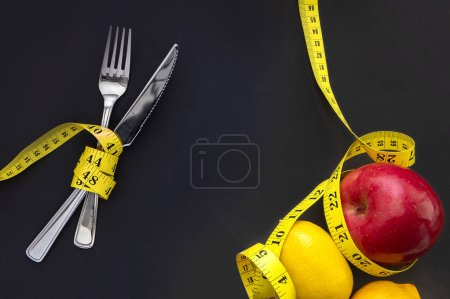 Photo for Cutlery, apple, lemons and measuring tape on a dark background. - Royalty Free Image