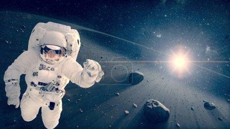 Photo pour Un astronaute volant dans un espace lointain. Scène spatiale. Ceinture de météorites à l'arrière-plan. Éléments de cette image fournis par la NASA . - image libre de droit