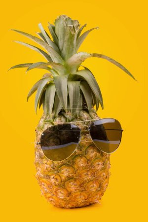 Photo for Trendy pineapple wearing hipster sunglasses on yellow background - Royalty Free Image