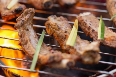 Marinated With BBQ Sauce Pork Spare Rib On The Hot Charcoal Grill With Bright Flames In The Background, Close Up