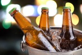 cold bottles of beer in bucket with ice on bokeh background