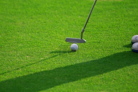 Feet of female golf player putting at green