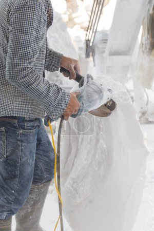 sculptor making sculpture of white marble