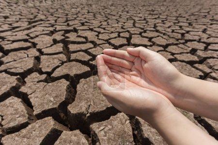 Photo pour L'eau à la main sur la terre ferme fissurée . - image libre de droit