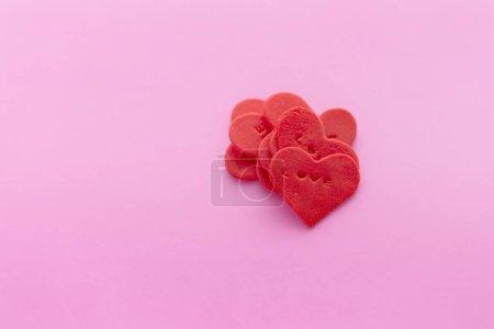 Coeur rouge en forme de sucre sur fond rose
