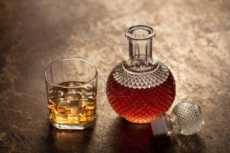 Photo pour Bouteille de whisky et verre de whisky avec glace sur fond noir - image libre de droit